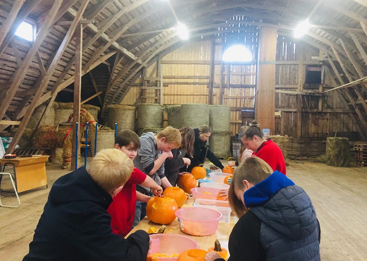 Barn och ledare gör halloween pumpor