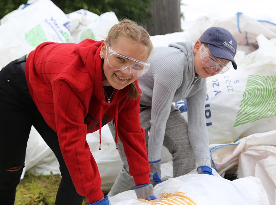 Flicka och pojke packar ihop gödselsäckar