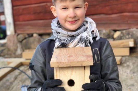 Pojke med en färdig fågelholk i handen