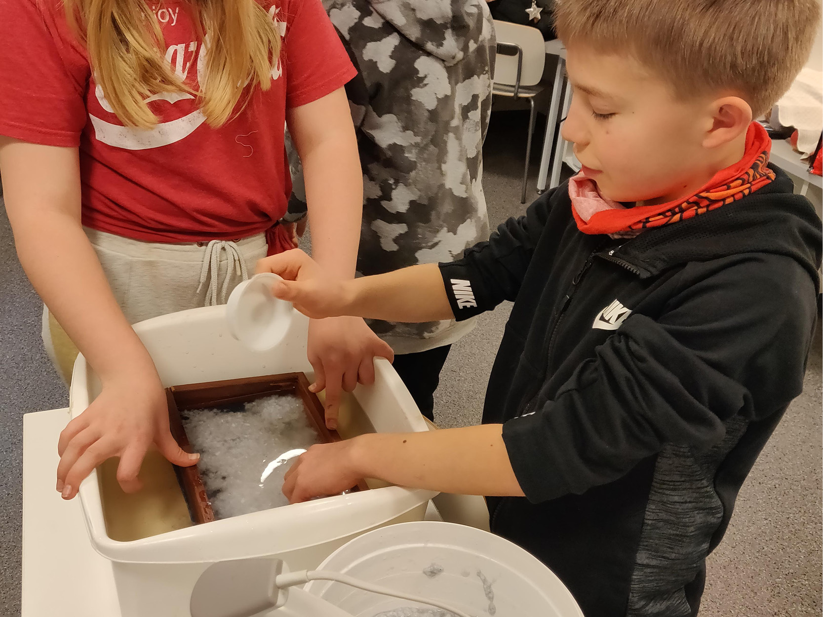 Pojke skopar pappersmassa i en ram
