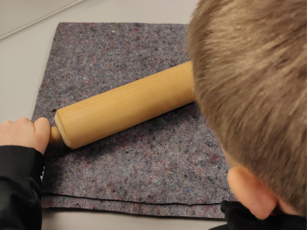 Pojke pressar ut vattnet från pappersmassan med kavel
